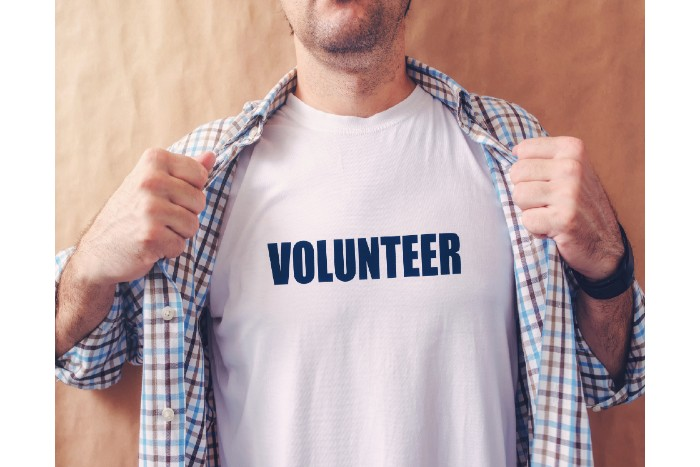 learn a new skill: a man wearing a shirt that says volunteer