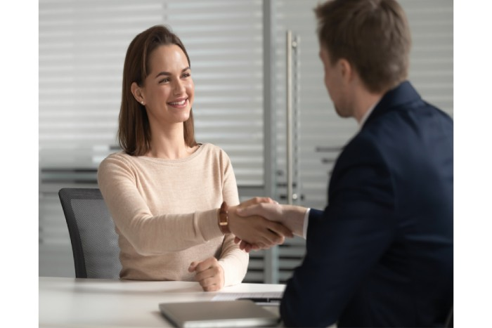 woman shaking hands with a man after getting employed